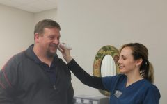 DMS Nurse Tabitha Sale takes Assistant Principal Rodney Strutton's temperature.