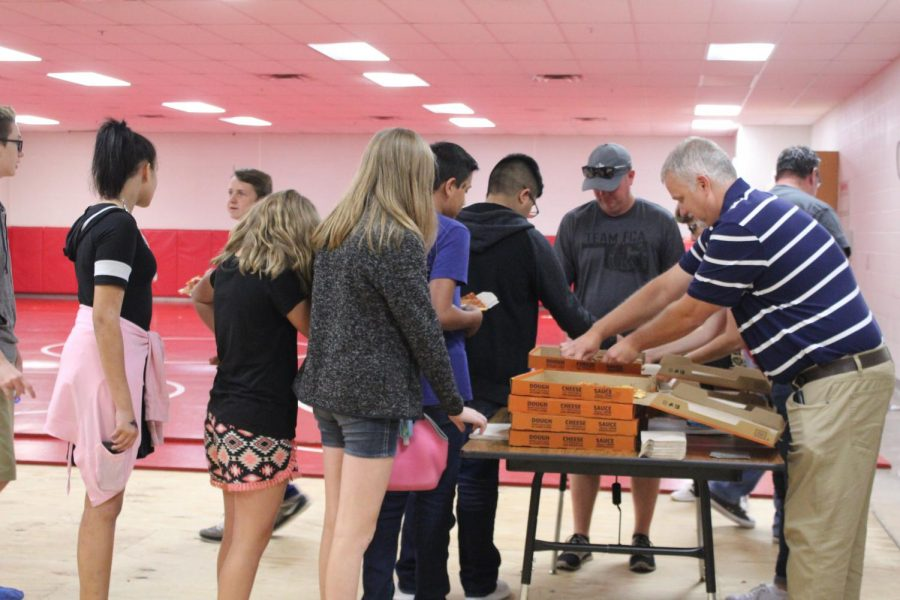 Mike Lewis passes out pizza to eighth-grade students during FCA.