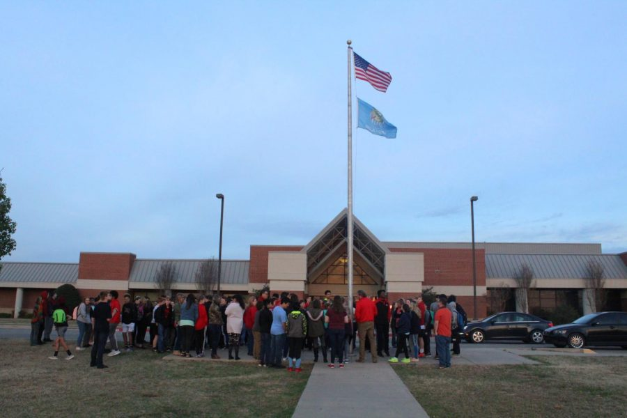 Students+and+teachers+gather+at+the+flag+pole+Wednesday+morning.