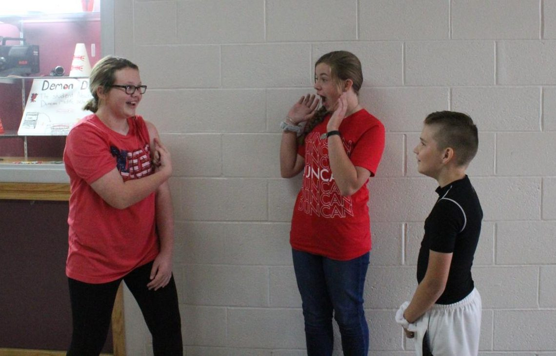 Bailee Howard illustrates the concerns of the dress code rule about showing shoulders to Emma Evans and Collin Sherrill.