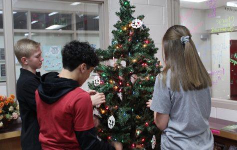 Eli Ramirez, Kooper Kelly, and Allie Shreckengost decorate the library's Christmas Tree.