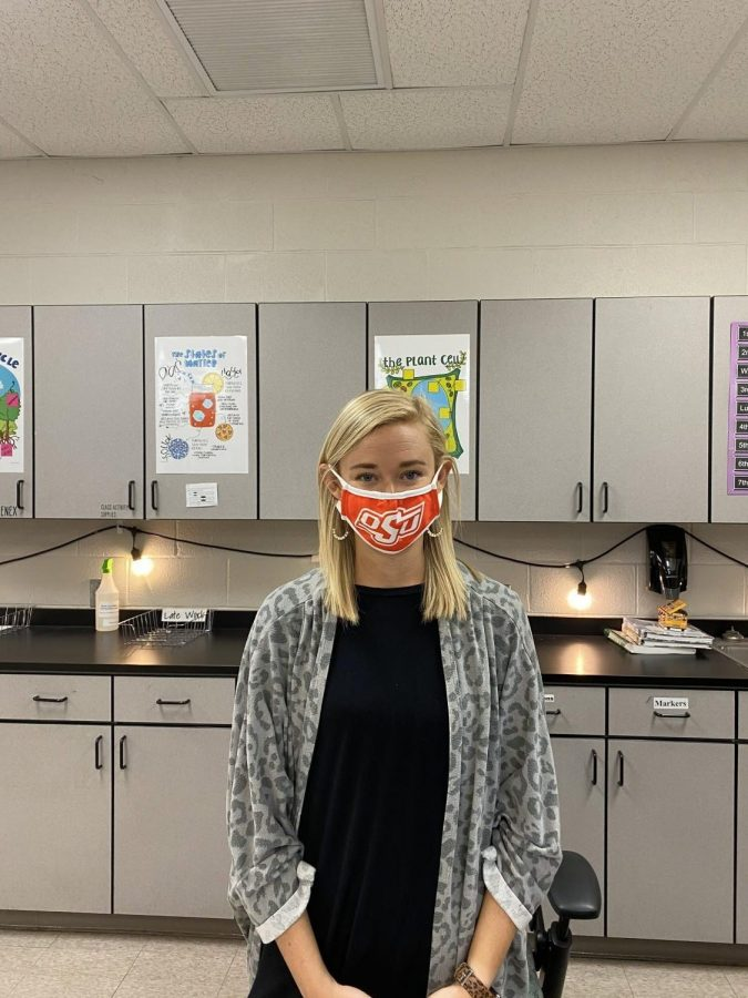 Emily Prichard smiles for a picture under a mask