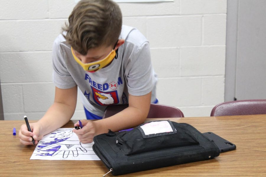 A student works on an art project in class. All students at Duncan Middle School are required to wear masks this year.