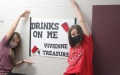 Vivienne Albin shows off her campaign poster at the end of the seventh-grade hall.