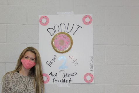 Ava Johnson poses by one of her campaign posters early in the Student Council campaign trail. Johnson was elected Student Council president today.