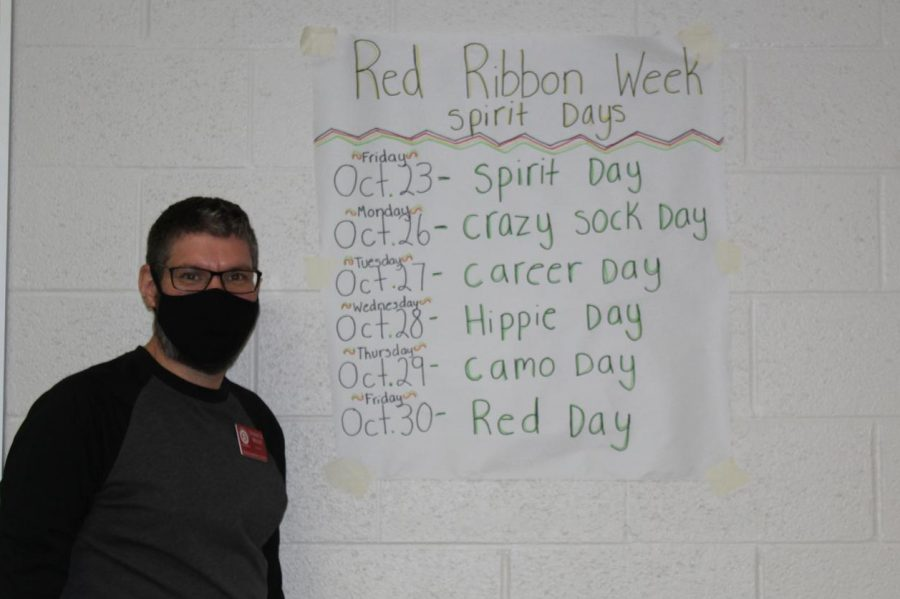 Derrick Miller, one of the NJHS sponsors at Duncan Middle School, shows off a poster of the dress-up days.