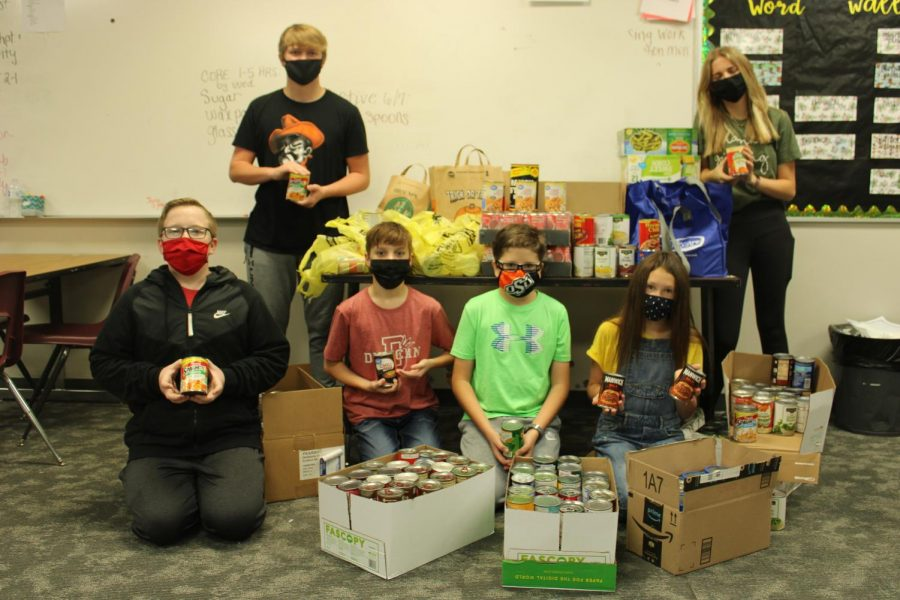 NJHS eighth-grade officers show off the food that was donated through the canned food drive.