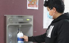 Armando Garcia-Diaz fills a water bottle using the new filter water station in the seventh-grade hall.