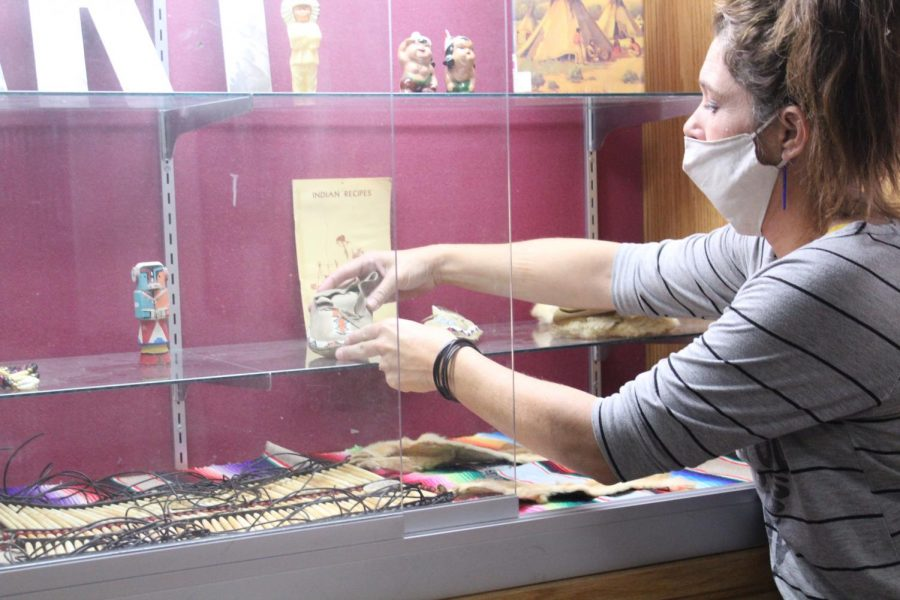 DMS art teacher Shelly Farrar decorates the trophy case next to the art room with Native American memorabilia.