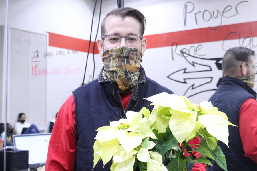 Mark Monteith shows off one of the poinsettia plants sold by the choir students.