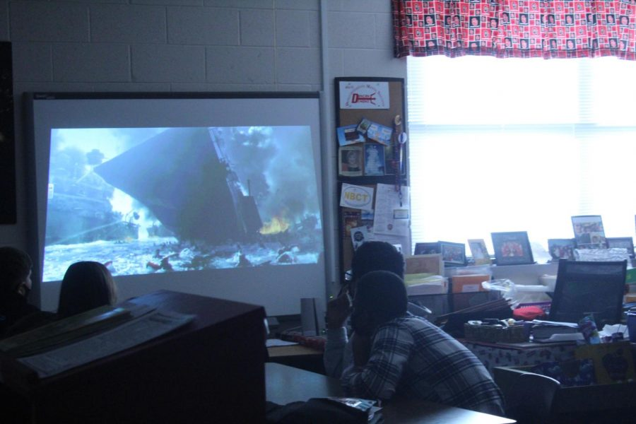Students in Cathy Barker's humanities class watch a scene from the movie