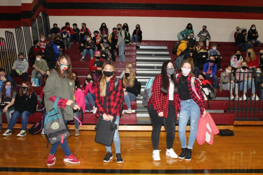 Students, dressed in their buffalo plaid gather together on the gym floor.