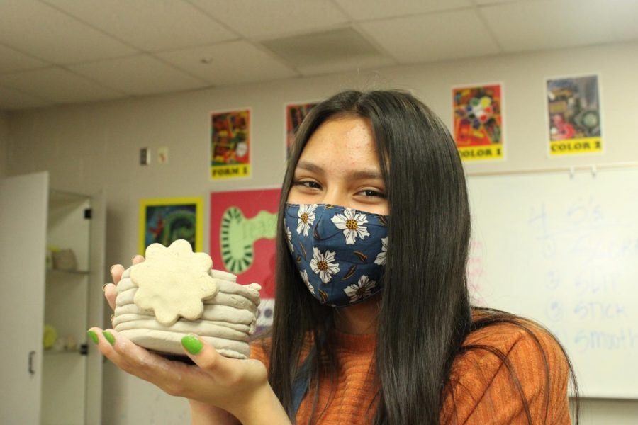 Christina Ward shows off her coil pot creation from art class.