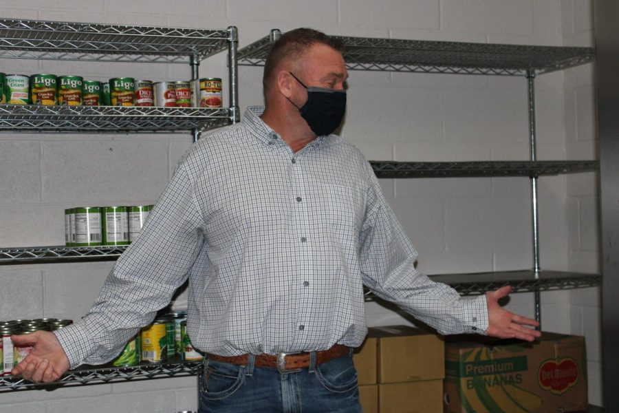 Counselor Bubba Clark shows off the empty shelves in the Duncan Middle School food pantry.