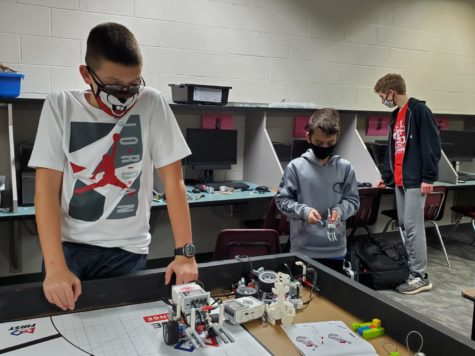 Jeremy Abel tests the coding of his robot, while Cooper Majure and Andrew Potts work on their own robot projects during a Robotics Team meeting. The state competition may be virtual this year, if it doesn