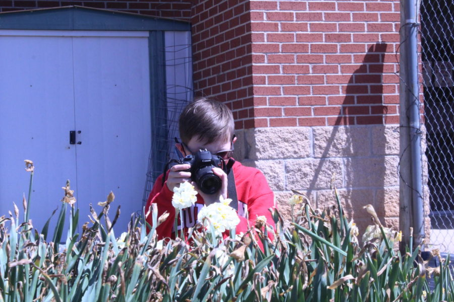 Cole Young takes pictures of flowers in the Duncan Middle School garden as part of a photography practice lesson in yearbook.